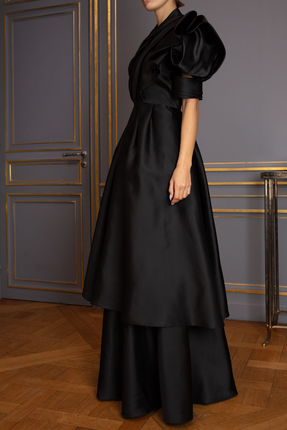 One-shouldered black satin tiered gown with sculptural sleeve